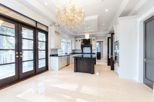 Mid-sized elegant u-shaped travertine floor and beige floor eat-in kitchen photo in Vancouver with an undermount sink, raised-panel cabinets, granite countertops, gray backsplash, stone tile backsplash, stainless steel appliances, an island and white cabinets
