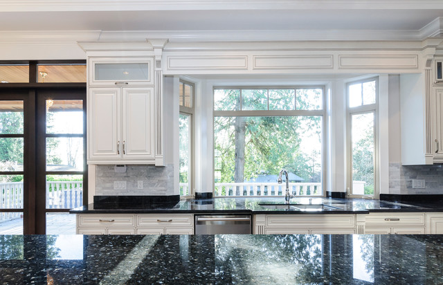 Inspiration for a mid-sized timeless u-shaped travertine floor and beige floor eat-in kitchen remodel in Vancouver with an undermount sink, raised-panel cabinets, granite countertops, gray backsplash, stone tile backsplash, stainless steel appliances, an island and white cabinets