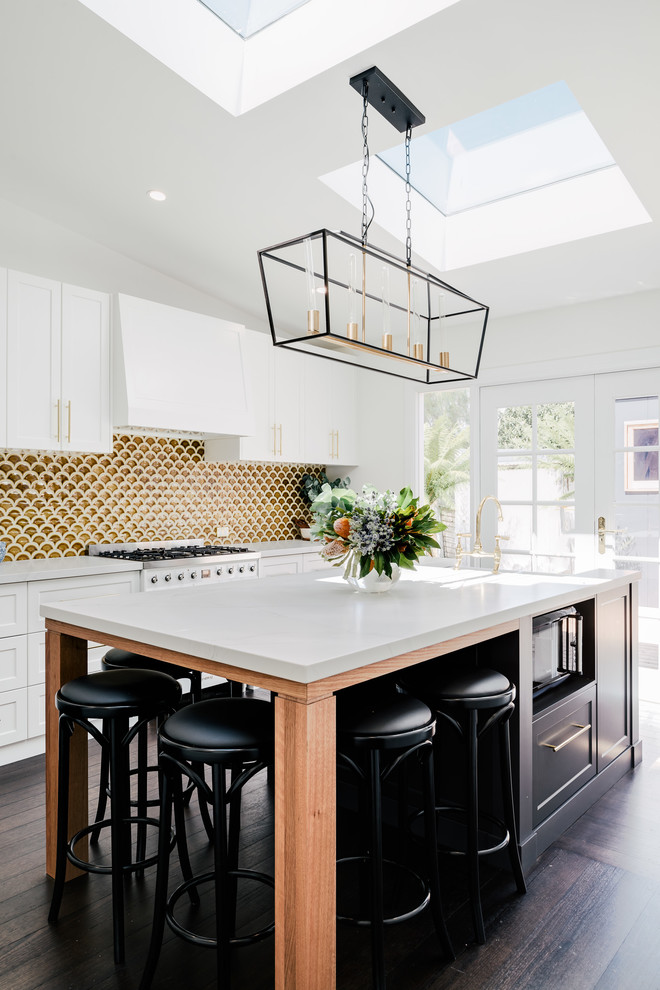 Large transitional galley eat-in kitchen in Hobart with a farmhouse sink, shaker cabinets, white cabinets, quartz benchtops, yellow splashback, ceramic splashback, stainless steel appliances, dark hardwood floors, an island, brown floor and white benchtop.