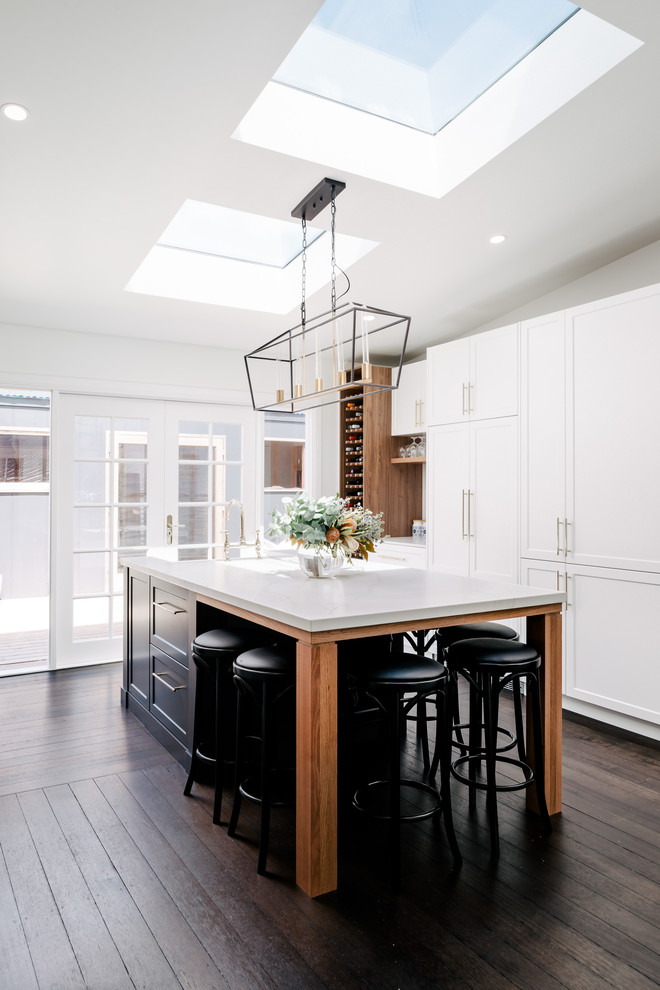 Inspiration for a large transitional galley eat-in kitchen in Hobart with a farmhouse sink, shaker cabinets, white cabinets, quartz benchtops, dark hardwood floors, an island, brown floor and panelled appliances.