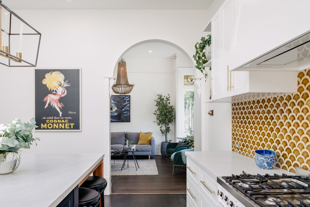 This is an example of a large transitional galley eat-in kitchen in Hobart with a farmhouse sink, shaker cabinets, white cabinets, quartz benchtops, yellow splashback, ceramic splashback, stainless steel appliances, dark hardwood floors, an island, brown floor and white benchtop.