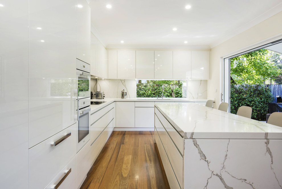 This is an example of a mid-sized contemporary l-shaped eat-in kitchen in Sydney with an undermount sink, flat-panel cabinets, white cabinets, quartz benchtops, white appliances, an island, multi-coloured splashback, window splashback and light hardwood floors.