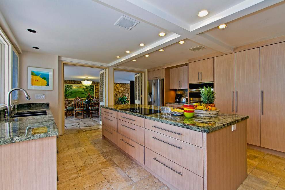 Large island style galley travertine floor and brown floor enclosed kitchen photo in Hawaii with a double-bowl sink, flat-panel cabinets, light wood cabinets, granite countertops, stainless steel appliances, an island and green countertops