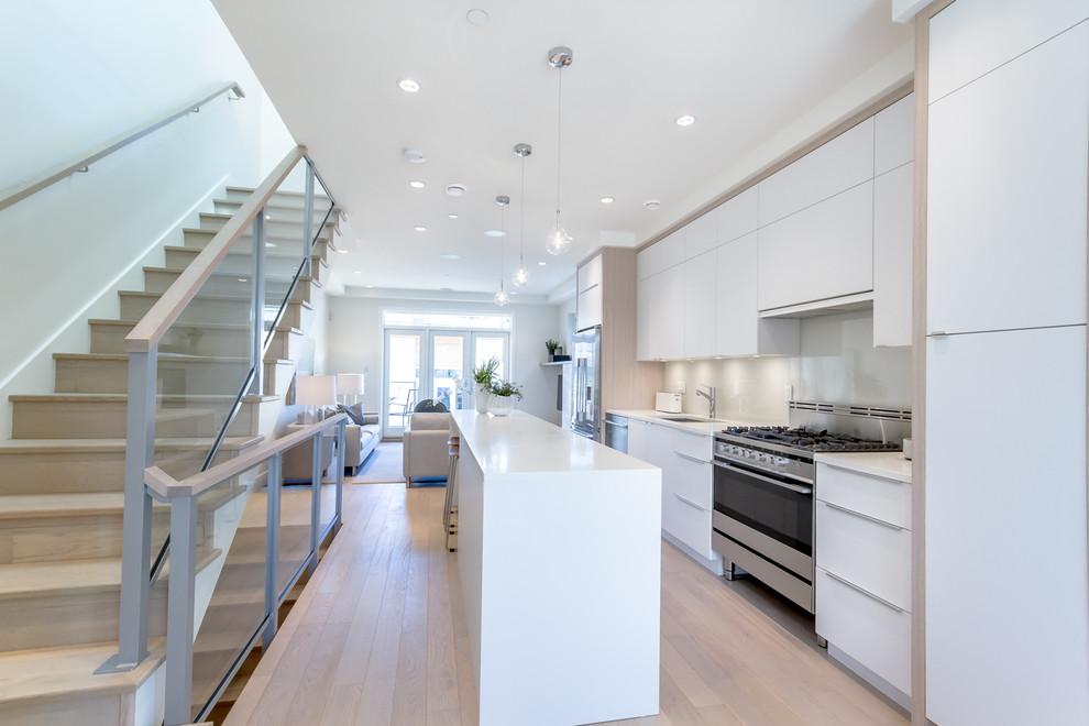 Diseño de cocina lineal, actual, con fregadero bajoencimera, armarios con paneles lisos, puertas de armario blancas, salpicadero verde y suelo de madera clara