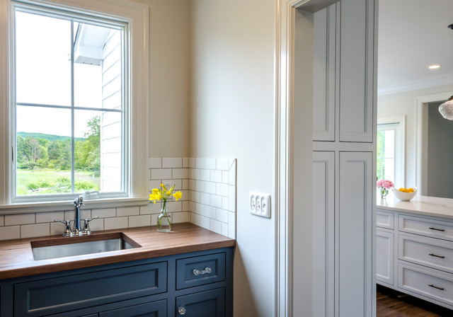 Example of a classic medium tone wood floor and brown floor kitchen design in Cleveland with shaker cabinets, gray backsplash, subway tile backsplash, stainless steel appliances and an island