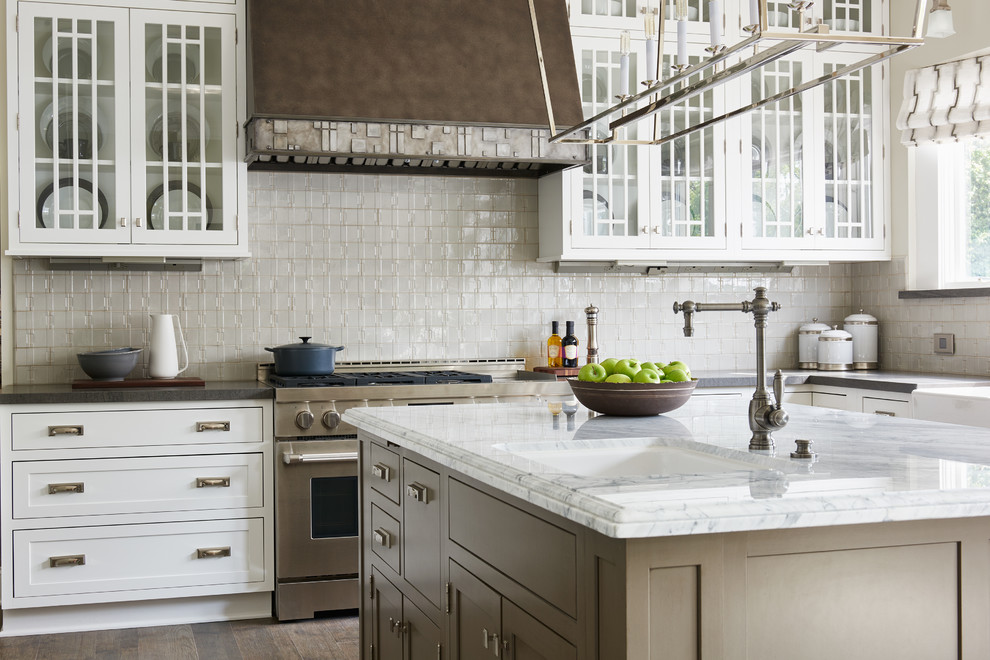 Transitional kitchen photo in Los Angeles with an undermount sink, glass-front cabinets, white cabinets, beige backsplash, stainless steel appliances and an island