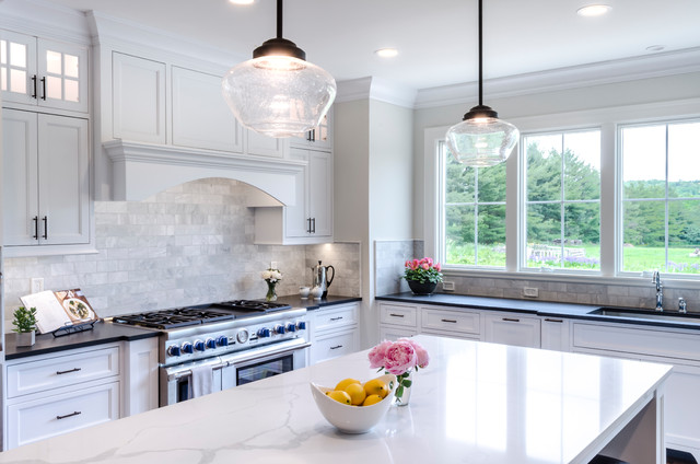 Kitchen - large traditional medium tone wood floor and brown floor kitchen idea in Cleveland with shaker cabinets, gray backsplash, subway tile backsplash, stainless steel appliances, an island, an undermount sink and white cabinets