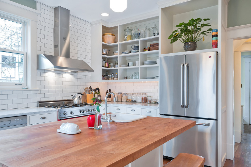 Example of a mid-sized country u-shaped carpeted and brown floor enclosed kitchen design in Seattle with a farmhouse sink, shaker cabinets, white cabinets, wood countertops, white backsplash, subway tile backsplash, stainless steel appliances, an island and brown countertops