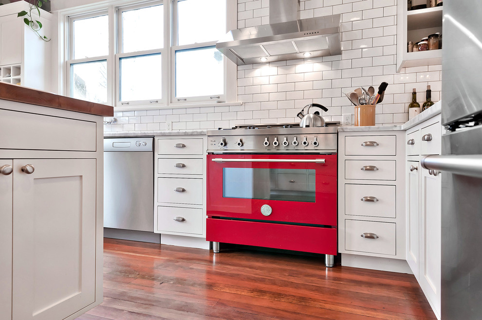 Enclosed kitchen - mid-sized country u-shaped carpeted and brown floor enclosed kitchen idea in Seattle with a farmhouse sink, shaker cabinets, white cabinets, wood countertops, white backsplash, subway tile backsplash, stainless steel appliances, an island and brown countertops