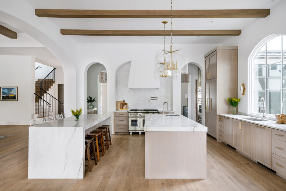 Inspiration for a huge mediterranean l-shaped light wood floor and beige floor kitchen remodel in Austin with an undermount sink, shaker cabinets, beige cabinets, white backsplash, paneled appliances, two islands and white countertops