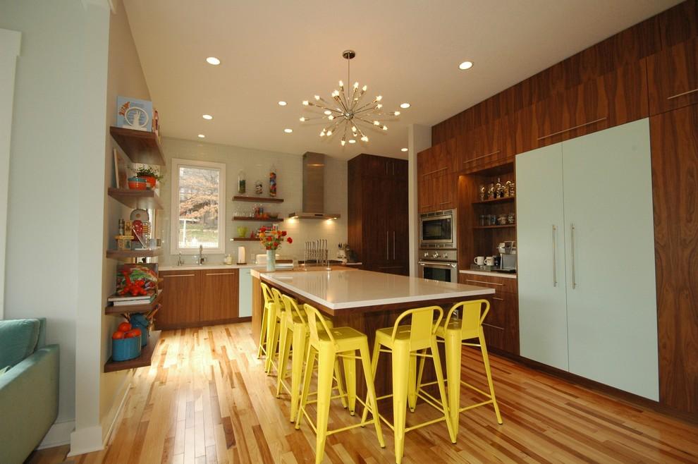 Example of a trendy u-shaped eat-in kitchen design in Kansas City with flat-panel cabinets, dark wood cabinets, white backsplash, subway tile backsplash, paneled appliances, a single-bowl sink and quartz countertops