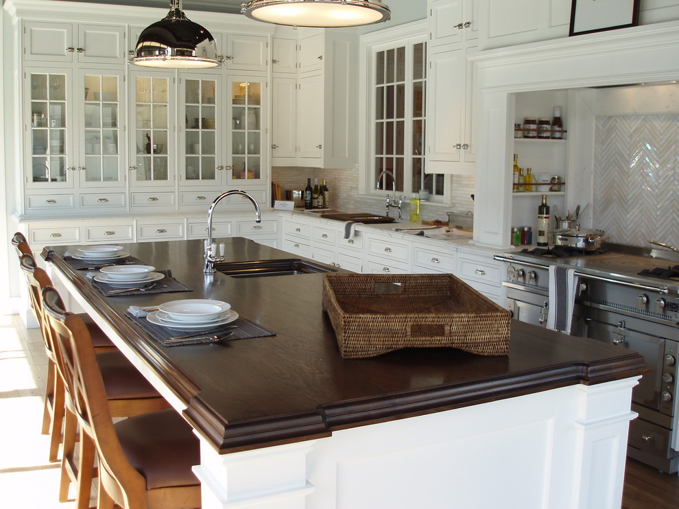 Elegant l-shaped eat-in kitchen photo in New York with glass-front cabinets, wood countertops and an undermount sink