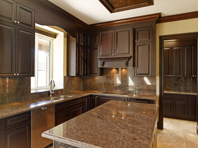Example of a mid-sized classic eat-in kitchen design in Vancouver with an undermount sink, raised-panel cabinets, dark wood cabinets, granite countertops, stone slab backsplash, stainless steel appliances and an island