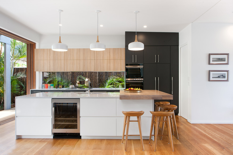 Inspiration for a contemporary medium tone wood floor kitchen remodel in Brisbane with an undermount sink, flat-panel cabinets, black cabinets, an island, quartz countertops and window backsplash