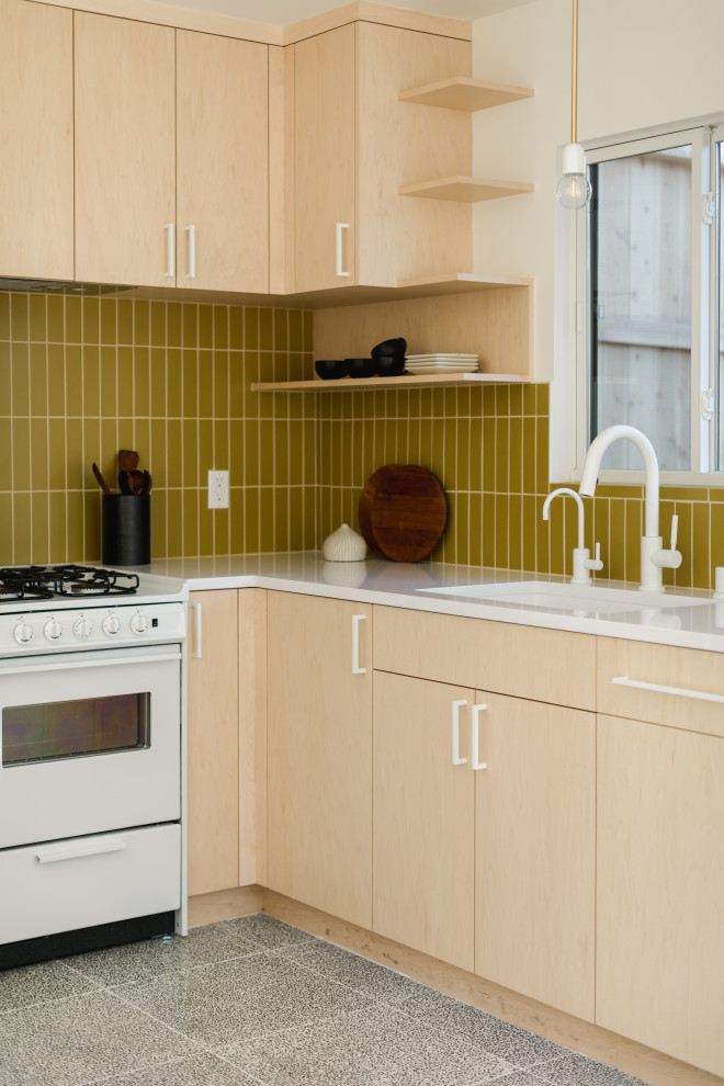 Small danish l-shaped concrete floor and gray floor kitchen photo in Los Angeles with yellow backsplash, ceramic backsplash, white appliances, no island, white countertops, an undermount sink, flat-panel cabinets and light wood cabinets