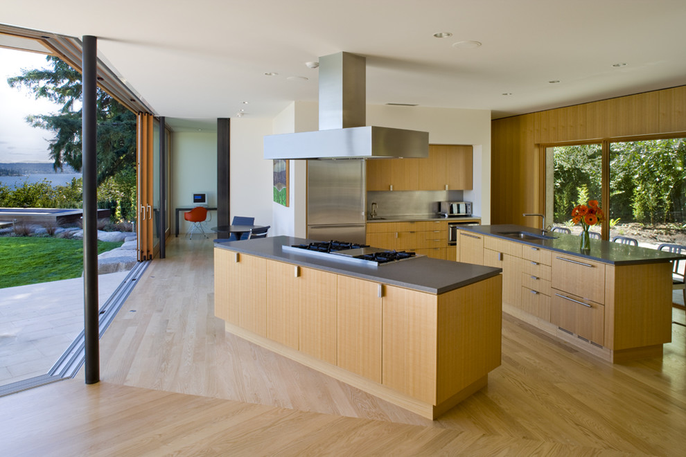 Kitchen - contemporary kitchen idea in Seattle with stainless steel appliances, an undermount sink, flat-panel cabinets, light wood cabinets and two islands