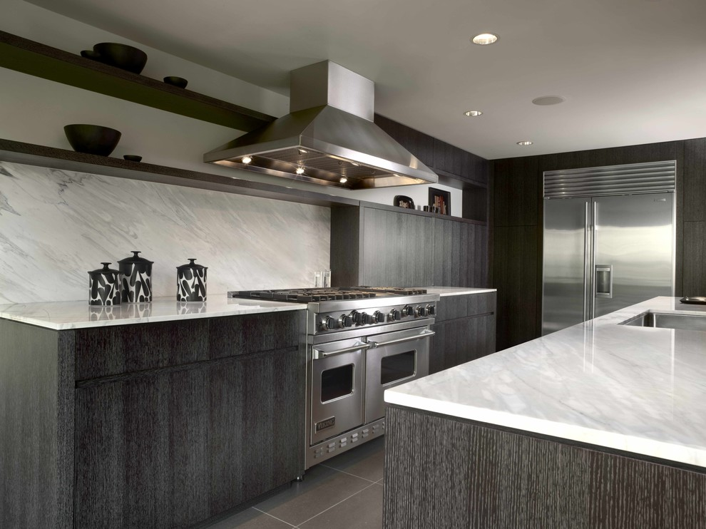 Trendy kitchen photo in Seattle with stainless steel appliances, marble countertops, an undermount sink, flat-panel cabinets, black cabinets, white backsplash and stone slab backsplash