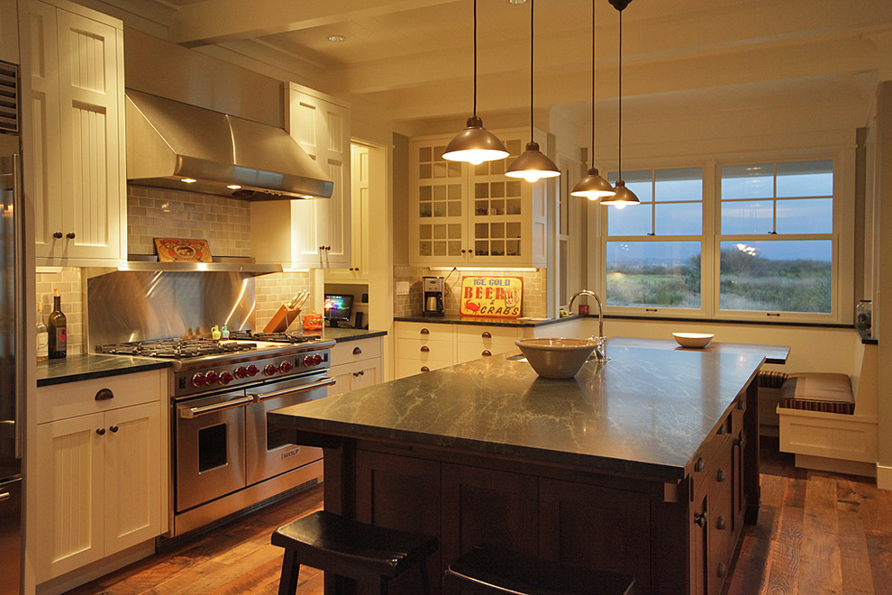 Example of a classic kitchen design in Seattle with glass-front cabinets, stainless steel appliances, white cabinets and soapstone countertops