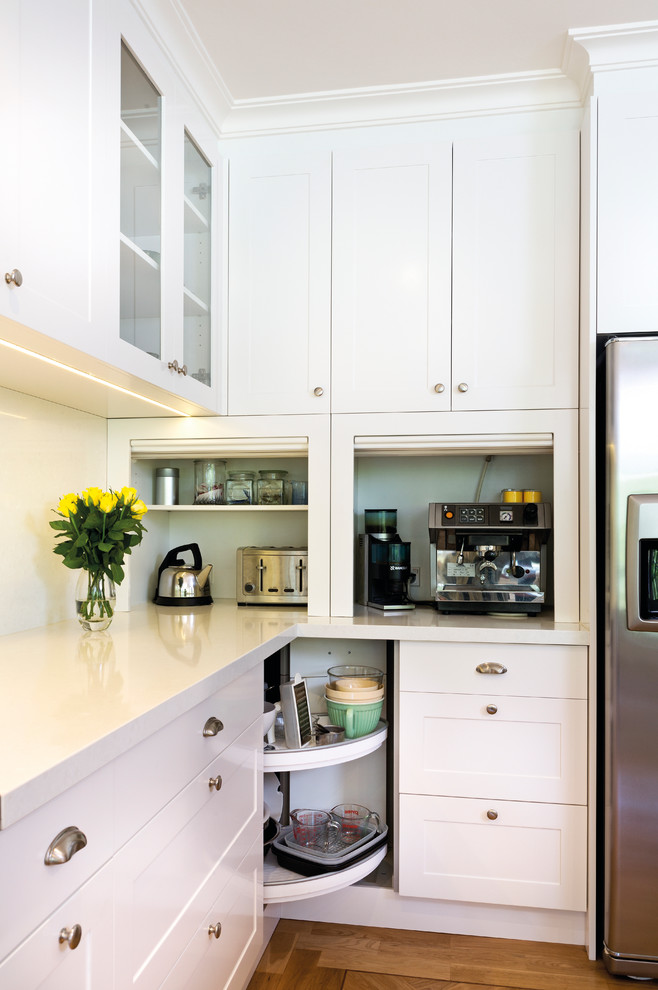 Transitional medium tone wood floor kitchen photo in Melbourne with shaker cabinets, white cabinets, stainless steel appliances, white backsplash, glass sheet backsplash and white countertops