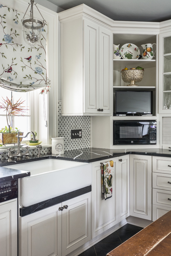 Elegant black floor kitchen photo in DC Metro with a farmhouse sink, recessed-panel cabinets, white cabinets, multicolored backsplash and black countertops