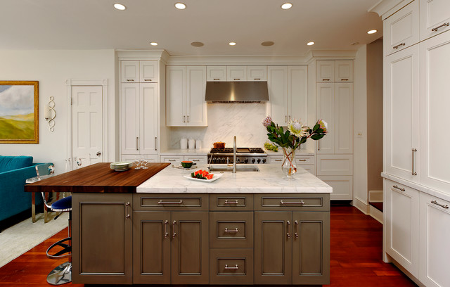 Inspiration for a mid-sized timeless l-shaped medium tone wood floor open concept kitchen remodel in DC Metro with an undermount sink, white cabinets, white backsplash, stainless steel appliances, an island, wood countertops, louvered cabinets and stone tile backsplash