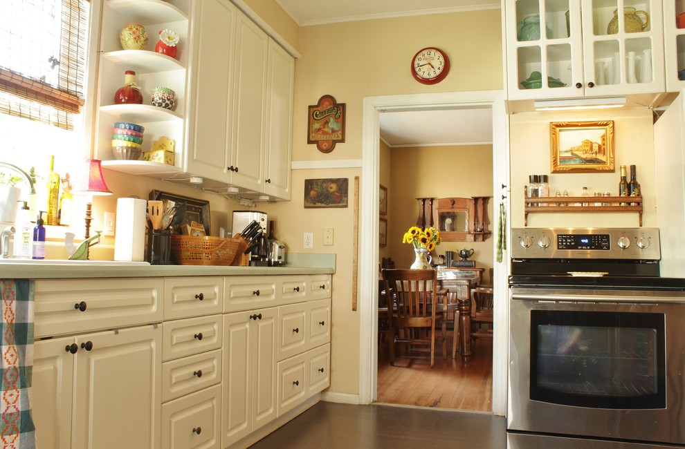 Inspiration for a mid-sized cottage linoleum floor enclosed kitchen remodel in Seattle with a drop-in sink, white cabinets, stainless steel appliances and no island