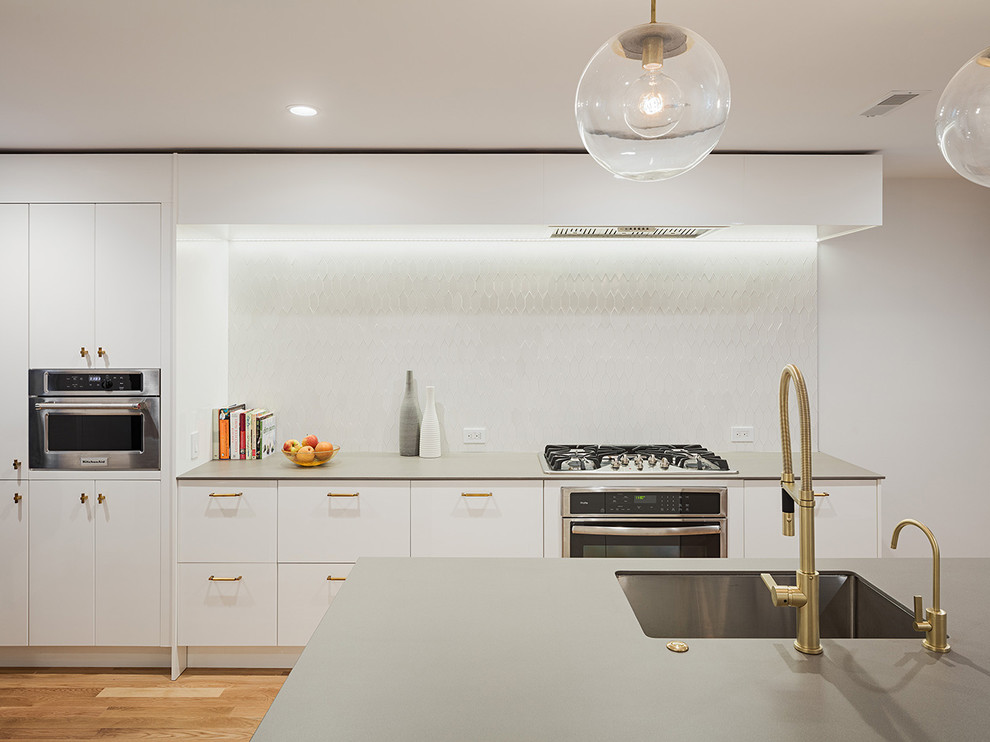 Trendy medium tone wood floor kitchen photo in Philadelphia with an undermount sink, flat-panel cabinets, white cabinets, white backsplash, stainless steel appliances and an island