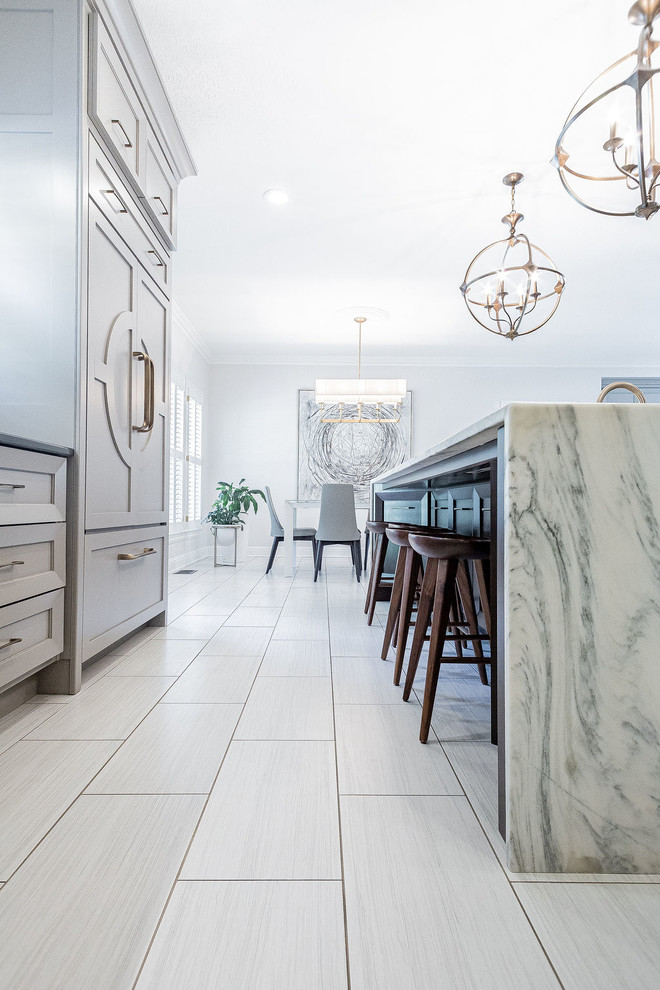 Example of a large minimalist u-shaped porcelain tile and gray floor kitchen design in Other with a farmhouse sink, gray cabinets, marble countertops, gray backsplash, marble backsplash, stainless steel appliances, an island and multicolored countertops