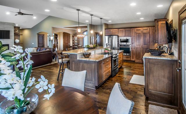 Inspiration for a mid-sized medium tone wood floor kitchen remodel in Other with an undermount sink, recessed-panel cabinets, medium tone wood cabinets, granite countertops, beige backsplash, ceramic backsplash, stainless steel appliances and an island