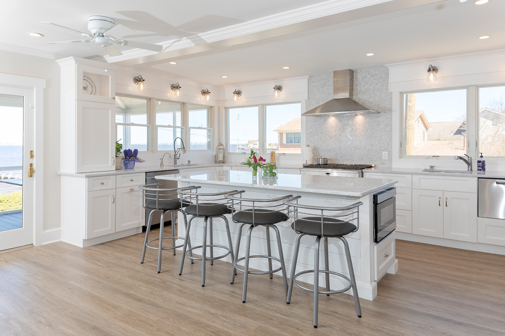 Mid-sized beach style u-shaped painted wood floor and brown floor eat-in kitchen photo in New York with an undermount sink, shaker cabinets, white cabinets, quartzite countertops, gray backsplash, marble backsplash, stainless steel appliances, an island and white countertops