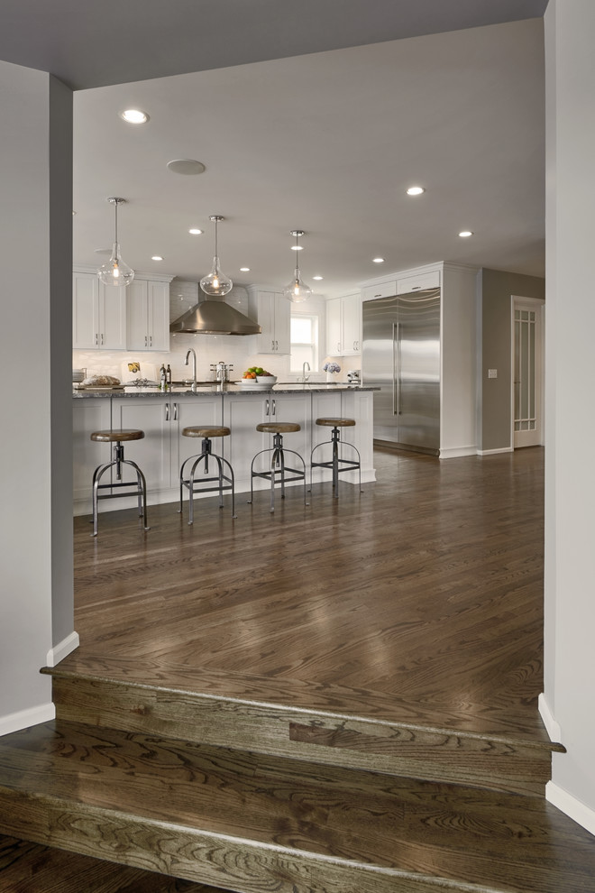 Eat-in kitchen - large craftsman l-shaped dark wood floor and brown floor eat-in kitchen idea in Seattle with a drop-in sink, shaker cabinets, white cabinets, white backsplash, ceramic backsplash, stainless steel appliances, an island, quartz countertops and gray countertops