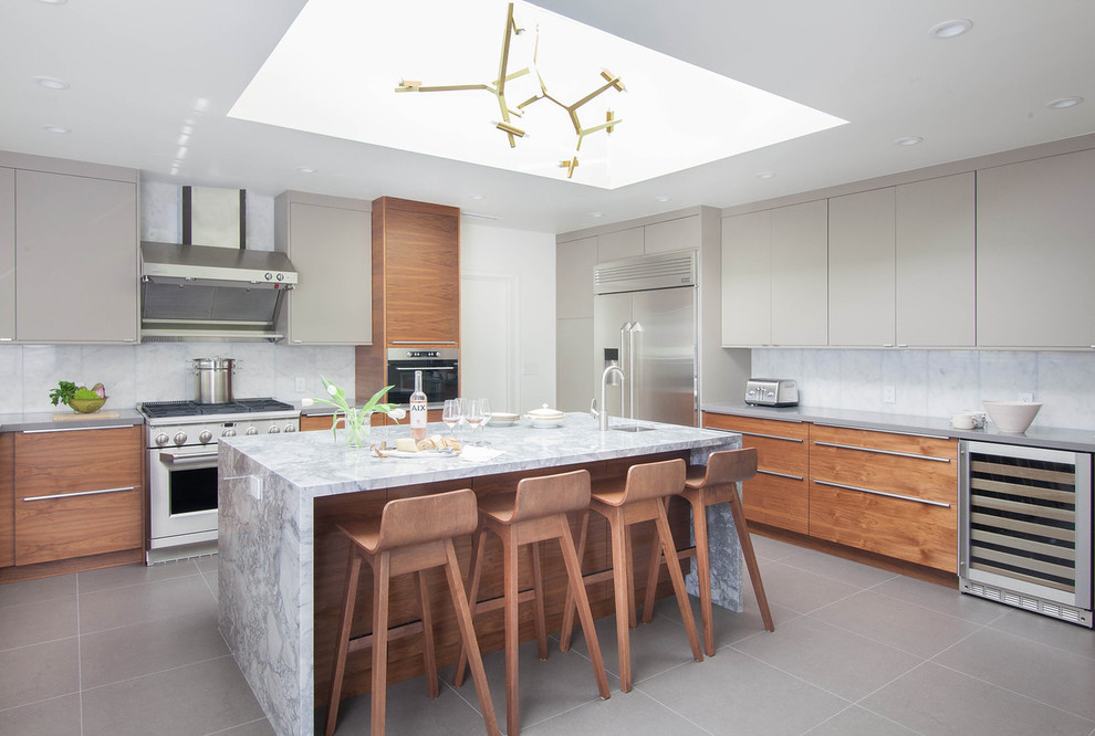 Example of a trendy porcelain tile and gray floor enclosed kitchen design in San Francisco with an undermount sink, flat-panel cabinets, medium tone wood cabinets, white backsplash, marble backsplash, stainless steel appliances, marble countertops and an island
