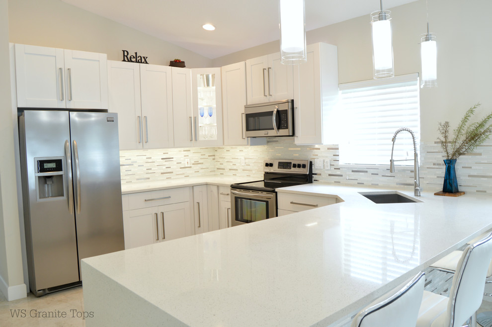Example of a kitchen design in Miami with an undermount sink, shaker cabinets, white cabinets, quartz countertops, stainless steel appliances and an island