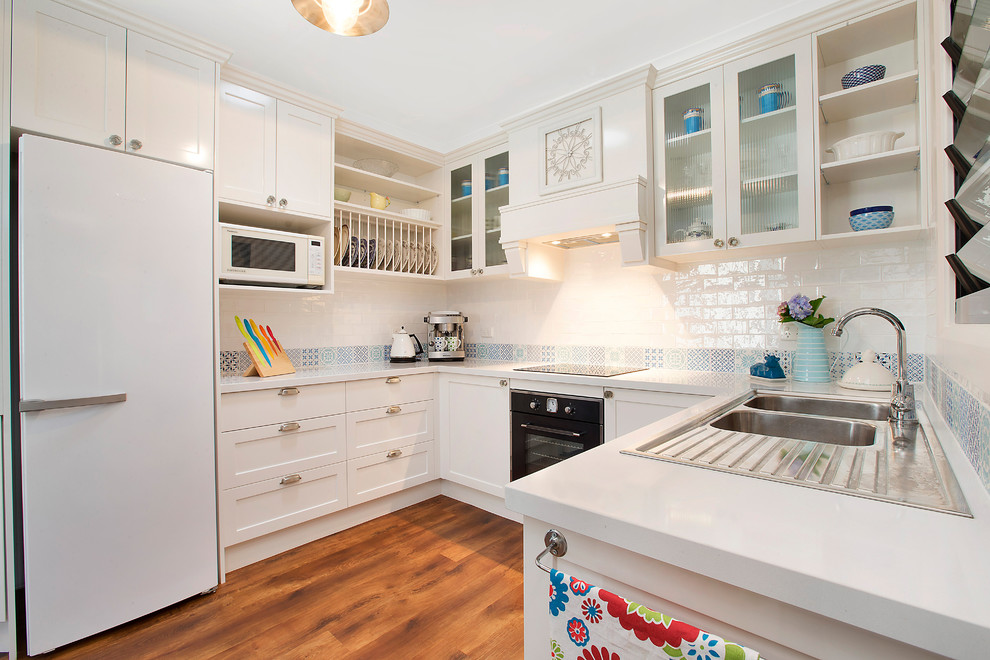 Inspiration for a timeless u-shaped dark wood floor kitchen remodel in Sydney with a drop-in sink, shaker cabinets, white cabinets, blue backsplash and no island