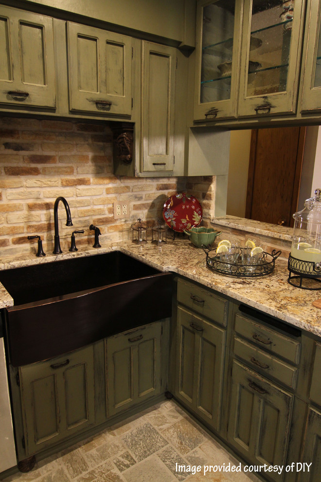 Inspiration for a small craftsman l-shaped slate floor enclosed kitchen remodel in Minneapolis with a farmhouse sink, recessed-panel cabinets, green cabinets, granite countertops, multicolored backsplash, brick backsplash and paneled appliances