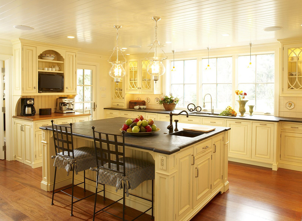 Example of a classic kitchen design in Philadelphia with yellow cabinets and soapstone countertops