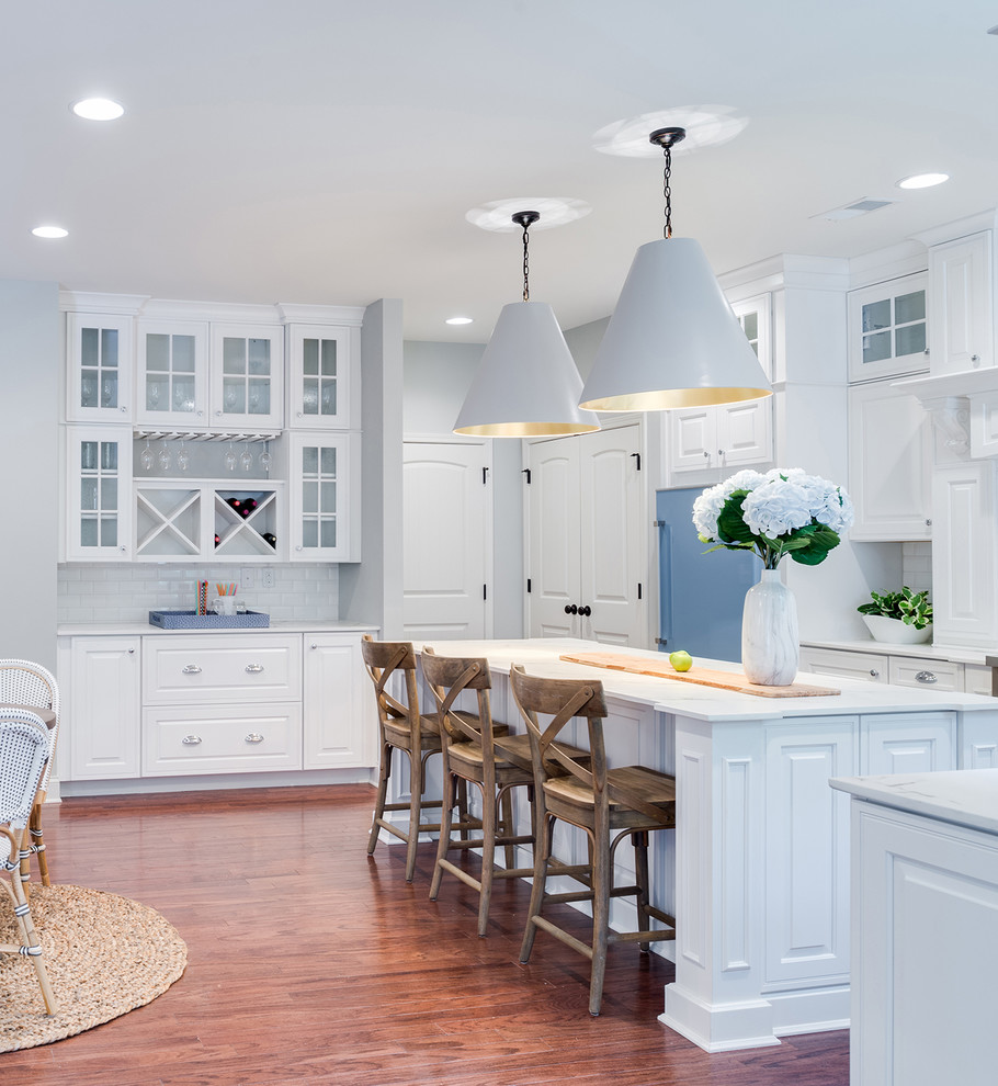 Eat-in kitchen - transitional l-shaped medium tone wood floor and brown floor eat-in kitchen idea in Orlando with raised-panel cabinets, white cabinets, white backsplash, subway tile backsplash, colored appliances, an island and white countertops