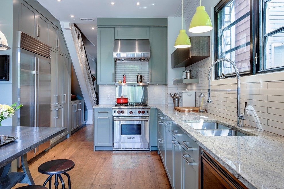 Example of a mid-sized ornate l-shaped eat-in kitchen design in Toronto with a double-bowl sink, green cabinets, granite countertops, white backsplash, porcelain backsplash, stainless steel appliances, shaker cabinets and no island
