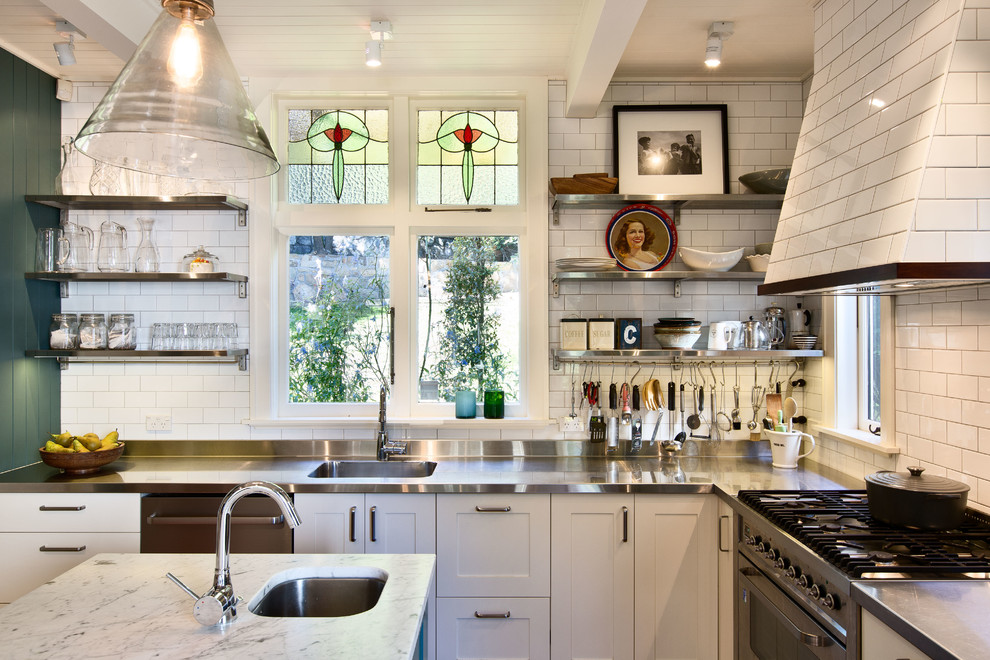 Example of an ornate u-shaped kitchen design in Auckland with an integrated sink, shaker cabinets, white cabinets, stainless steel countertops, white backsplash, subway tile backsplash and stainless steel appliances