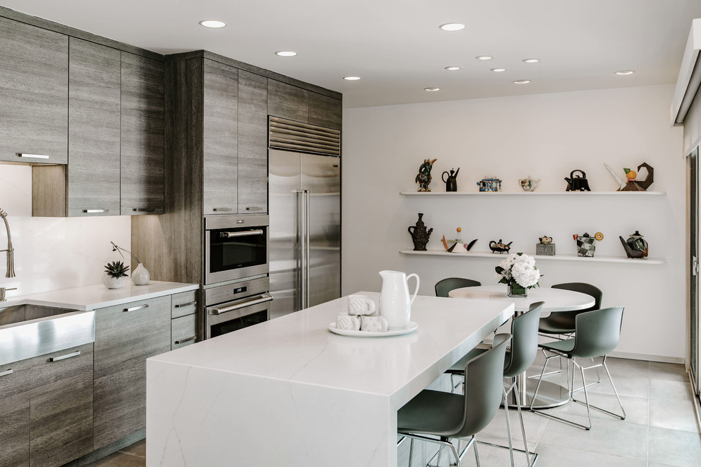 Example of a mid-sized trendy l-shaped porcelain tile and gray floor eat-in kitchen design in Detroit with a farmhouse sink, flat-panel cabinets, gray cabinets, quartz countertops, white backsplash, stainless steel appliances, an island and white countertops