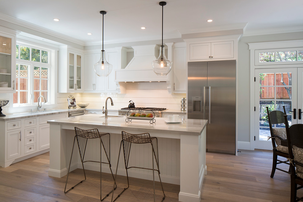 Eat-in kitchen - large transitional l-shaped medium tone wood floor eat-in kitchen idea in San Francisco with recessed-panel cabinets, white cabinets, stainless steel appliances and an island