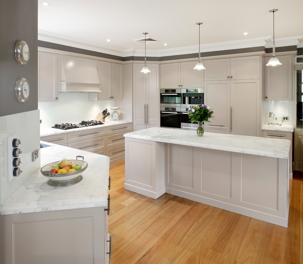 Mid-sized transitional galley medium tone wood floor kitchen photo in Sydney with white cabinets, a double-bowl sink, shaker cabinets, marble countertops, white backsplash, glass sheet backsplash, stainless steel appliances and an island