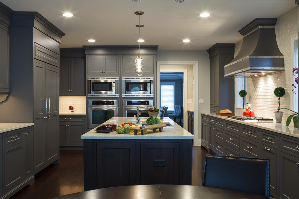Inspiration for a transitional u-shaped eat-in kitchen remodel in Chicago with an undermount sink, recessed-panel cabinets, gray cabinets, beige backsplash and paneled appliances