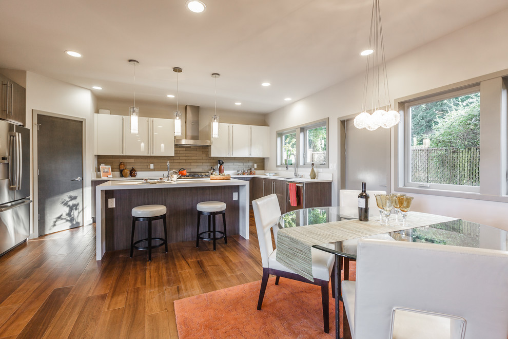 Trendy u-shaped eat-in kitchen photo in Seattle with flat-panel cabinets, white cabinets, beige backsplash and stainless steel appliances