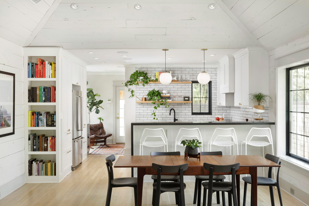 Farmhouse u-shaped light wood floor and beige floor eat-in kitchen photo in Houston with shaker cabinets, white cabinets, white backsplash, a peninsula and black countertops