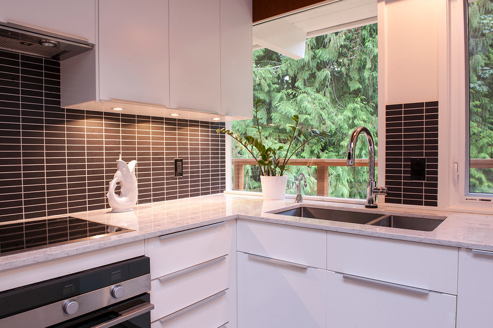 Eat-in kitchen - mid-sized 1950s u-shaped ceramic tile eat-in kitchen idea in Vancouver with a drop-in sink, flat-panel cabinets, white cabinets, quartz countertops, black backsplash, subway tile backsplash and stainless steel appliances