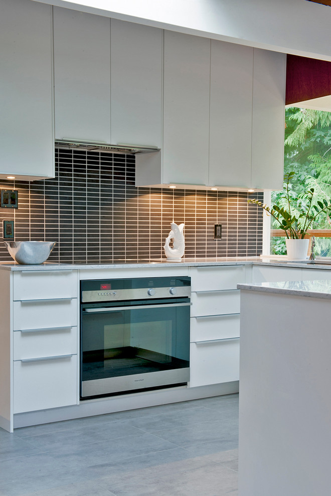 Inspiration for a mid-sized 1960s u-shaped ceramic tile eat-in kitchen remodel in Vancouver with a drop-in sink, flat-panel cabinets, white cabinets, quartz countertops, black backsplash, subway tile backsplash and stainless steel appliances