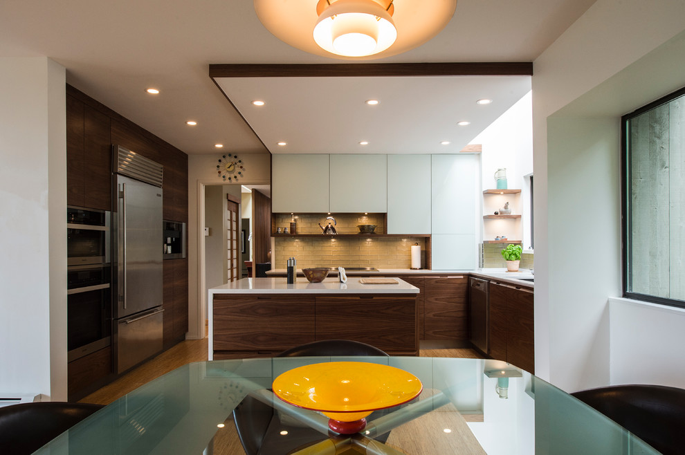 Example of a mid-sized eclectic u-shaped bamboo floor and beige floor eat-in kitchen design in Vancouver with an undermount sink, flat-panel cabinets, dark wood cabinets, quartz countertops, green backsplash, glass tile backsplash, stainless steel appliances and an island