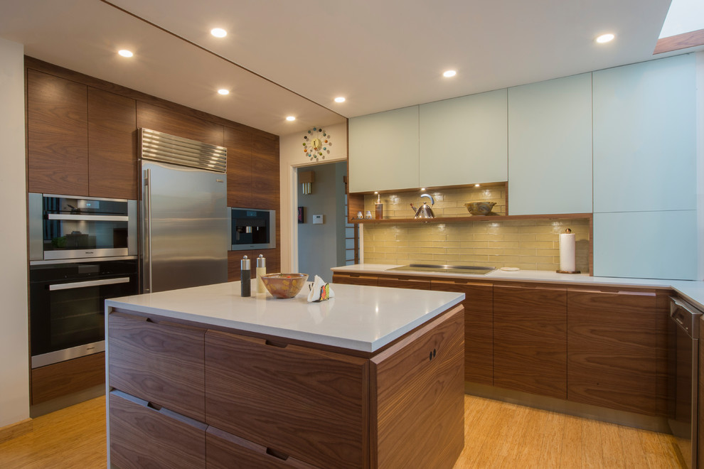 Mid-sized minimalist u-shaped bamboo floor and beige floor eat-in kitchen photo in Vancouver with an undermount sink, flat-panel cabinets, dark wood cabinets, quartz countertops, green backsplash, glass tile backsplash, stainless steel appliances and an island