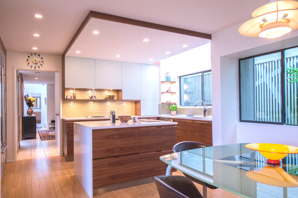 Eat-in kitchen - mid-sized modern u-shaped bamboo floor and beige floor eat-in kitchen idea in Vancouver with an undermount sink, flat-panel cabinets, dark wood cabinets, quartz countertops, green backsplash, glass tile backsplash, stainless steel appliances and an island
